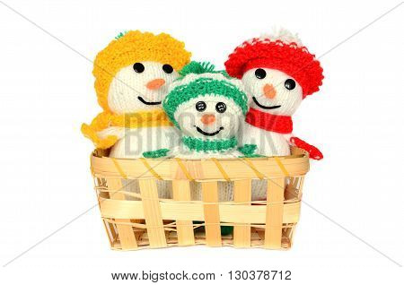 Knitted toys in a wicker basket on a white background