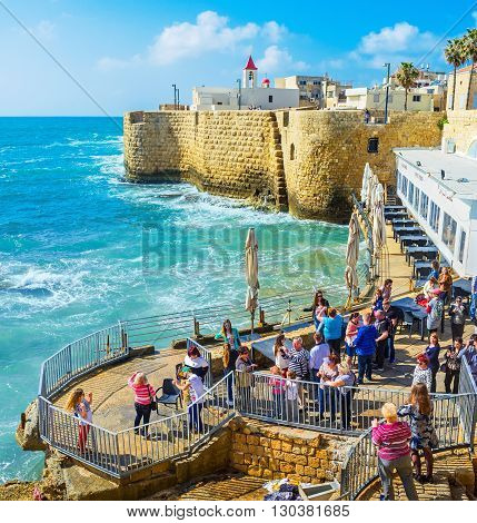 ACRE ISRAEL - FEBRUARY 20 2016: The tourists in the coastal viewpoint enjoy the Akko sea walls preserved since the Middle Ages on February 20 in Acre.