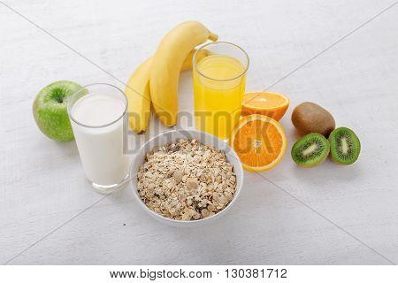 Granola with fruit juice and milk on a light wooden table. Set of healthy food