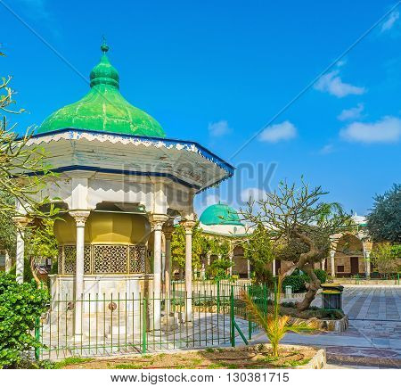 ACRE ISRAEL - FEBRUARY 20 2016: The green domed small sabil located in the courtyard of Al-Jazzar mosque among the trees and bushes of the lush garden on February 20 in Acre.