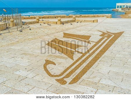 The stone sailing ship on the floor in the seaside promenade of Acre Israel.