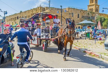 ACRE ISRAEL - FEBRUARY 20 2016: The tourist carriage tries to ride inthe narrow port promenade of old Akko on February 20 in Acre.