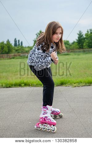 portrait of a young girl who rides rollerblade on asphalt