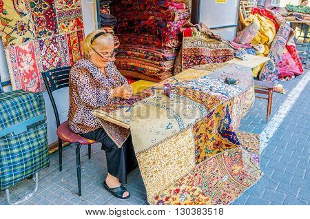 TEL AVIV ISRAEL - FEBRUARY 25 2016: The elderly seamstress makes patchwork rugs from kilim pieces stitched together in the flea market of Jaffa on February 25 in Tel Aviv.