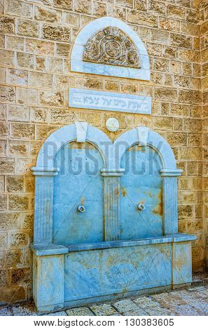 TEL AVIV ISRAEL - FEBRUARY 25 2016: The old marble fountain with the hebrew inscriptions and patterned relief is built in the old house wall on February 25 in Tel Aviv.