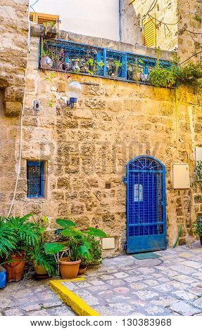 The old stone cottage with the bright blue door decorated with the plants in pots Jaffa Tel Aviv Israel.