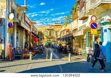 TEL AVIV ISRAEL - FEBRUARY 25 2016: The shady street of old Jaffa hides the cozy outdoor cafes and shops of retro furniture so popular in the local flea market on February 25 in Tel Aviv.