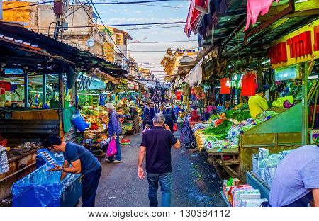 TEL AVIV ISRAEL - FEBBRUARY 25 2016: The noisy and crowded Carmel Market in Yemenite quarter is one of the city landmarks offering fresh vegetables fruits and local food on February 25 in Tel Aviv.