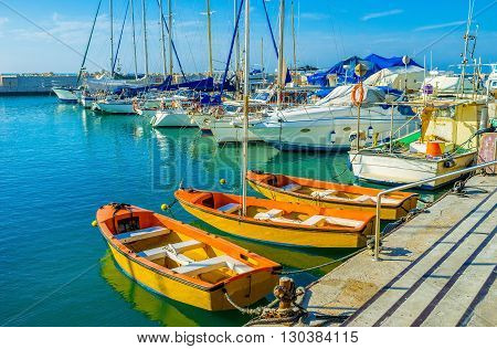 The orange tourist boats moored in old port of Jaffa Tel Aviv Israel.