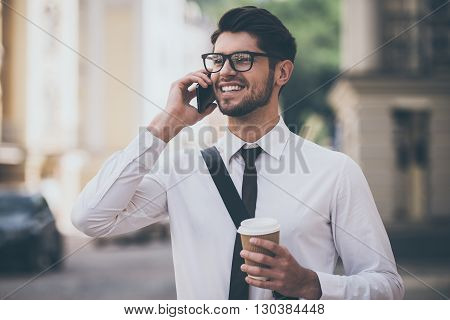 Business talk on a go. Cheerful young man in glasses holding coffee cup and talking on mobile phone with smile while walking outdoors