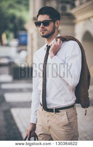 Ready for a date. Handsome young man holding jacket and looking away while walking outdoors