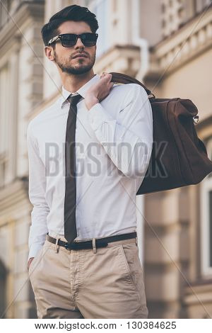 Trendy and handsome. Low angle view of handsome young man holding leather bag and looking away while walking outdoors