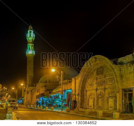 TEL AVIV ISRAEL - FEBBRUARY 25 2016: The evening view of Mahmoudiya Mosque with the bright illuminated minaret and its stone sabil on February 25 in Tel Aviv.