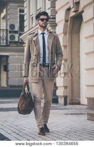 Elegance and style. Full length handsome young man  holding leather bag and looking away while walking outdoors