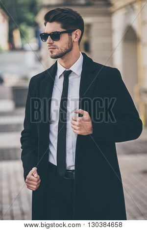 Stylish and handsome. Handsome young well-dressed man adjusting his coat and looking away while standing outdoors