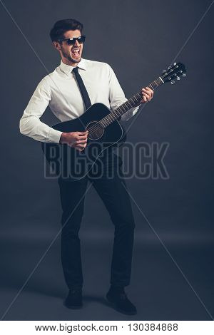 Rock or business star? Full length of handsome well-dressed young man playing guitar and keeping mouth open while standing against grey background