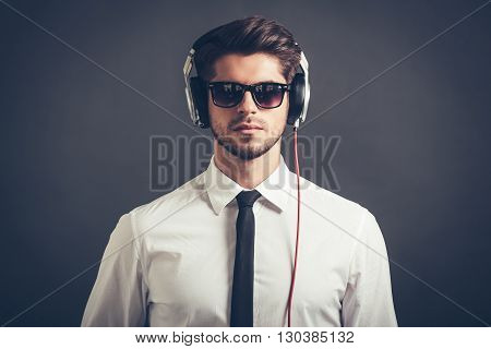 Feel his beat. Portrait of handsome well-dressed young man in headphones looking at camera while standing against grey background