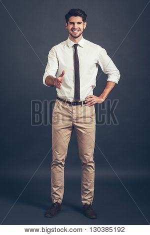 Nice to meet you! Full length of confident young handsome man reaching out his hand in greeting you and looking at camera with smile while standing against grey background