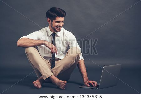 Staying online. Full length of confident young handsome man using laptop with smile while sitting on the floor against grey background