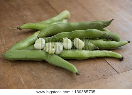 Fresh broad beans on a wooden surface