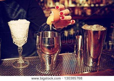 Bartender is adding egg yolk to the glass, toned image