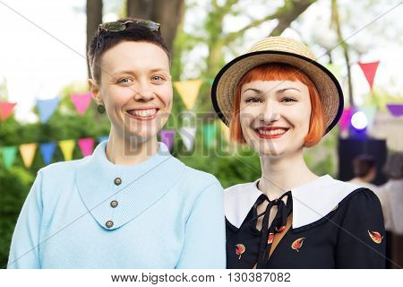 two smiling and cute girls in retro attire