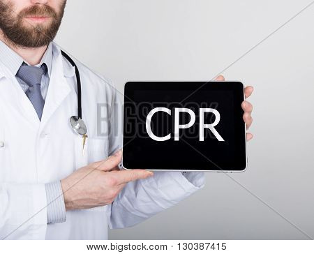 technology, internet and networking in medicine concept - Doctor holding a tablet pc with cpr sign. Internet technologies in medicine.
