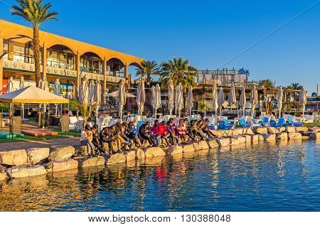 EILAT ISRAEL - FEBRUARY 24 2016: The group of religious tourists come to the North beach to read the Bible and pray at the time of sunrise on February 24 in Eilat.