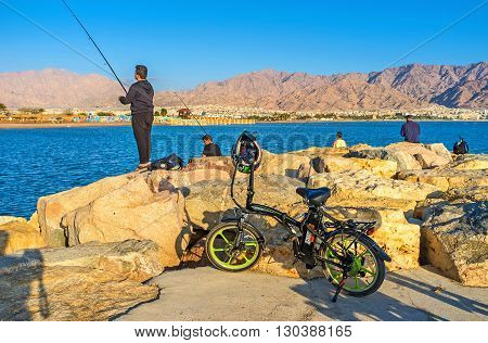 EILAT ISRAEL - FEBRUARY 24 2016: The fishermen enjoy the mountain landscapes and amazing nature from the stone pier on February 24 in Eilat.