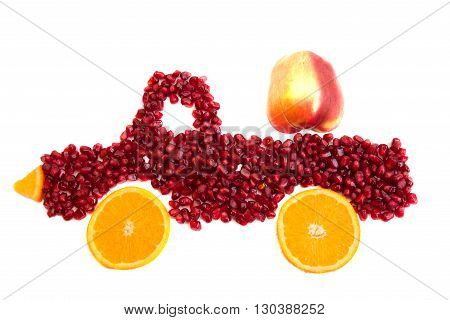 Seeds of pomegranate and slices of orange are as shape of lorry with apple