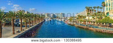 EILAT ISRAEL - FEBRUARY 23 2016: The entrance to marina surrounded by promenades with palms cafes restaurants and shopping centers on February 23 in Eilat.
