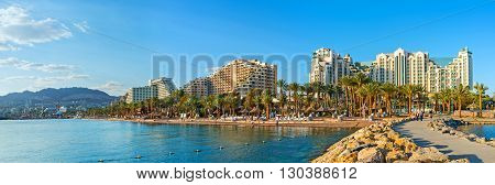 EILAT ISRAEL - FEBRUARY 24 2016: The pier is the perfect viewpoint overlooking the coast of the resort its central beach palm gardens and luxury hotels on February 24 in Eilat.