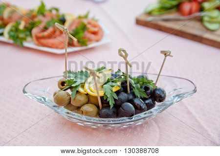 olives with slices of lemon and greenery on the saucer