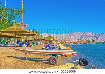 EILAT ISRAEL - FEBRUARY 23 2016: The Hananya Beach with many sunshades sun beds and the surfboard on February 23 in Eilat.