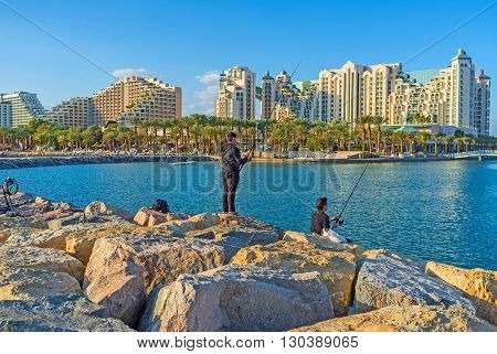 EILAT ISRAEL - FEBRUARY 24 2016: The local teenagers go fishing from the pier with the view on luxury hotels of resort on February 24 in Eilat.