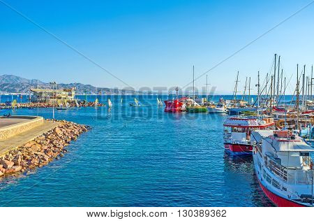 EILAT ISRAEL - FEBRUARY 23 2016: The yachts and tourist ships in harbor with the windsurfs coming back from the competitions on the background on February 23 in Eilat.