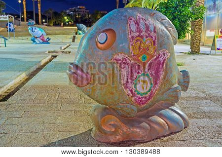 EILAT ISRAEL - FEBRUARY 23 2016: The sculpture of the fish decorated with hamsa protective symbol is located in the street in front of Eilat Museum on February 23 in Eilat.