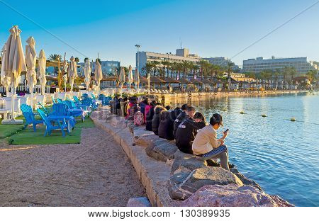 EILAT ISRAEL - FEBRUARY 24 2016: The religious tourists prays watching sunrise at the North beach on February 24 in Eilat.