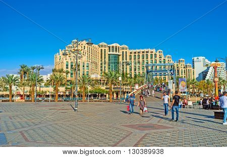 EILAT ISRAEL - FEBRUARY 23 2016: The wide central promenade with the Memorial drawbridge across Lagoona and Hilton Hotel Complex on the background on February 23 in Eilat.