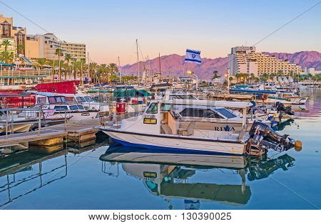 EILAT ISRAEL - FEBRUARY 23 2016: The motor boats and yachts in Lagoona with the scenic rocky mountains of Jordan in the sunset lights on February 23 in Eilat.