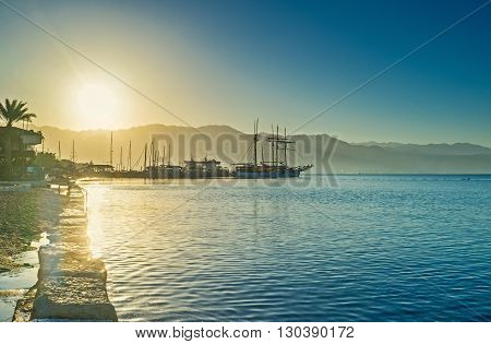 The sailing yachts in bright beams of the sunrise Eilat Israel.