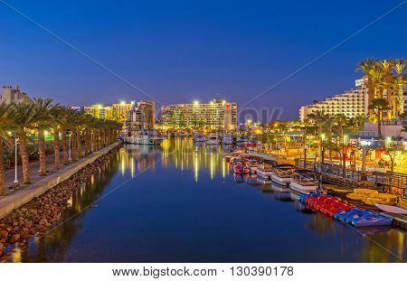 EILAT ISRAEL - FEBRUARY 24 2016: The romantic evening promenade along marina with moored boats and yachts on February 24 in Eilat.