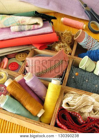 Wooden box with many colorful sewing accessories