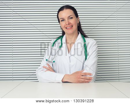 Female Doctor Sitting At Desk In Office