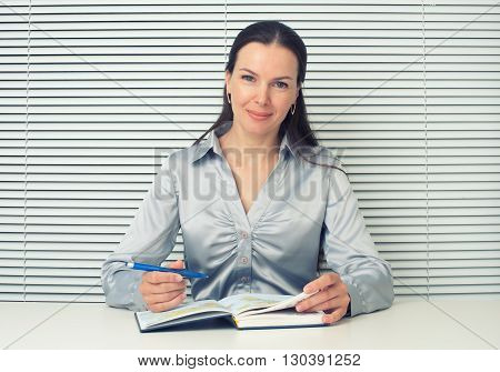 Smiling Brunette Woman Sitting At The Office Desk