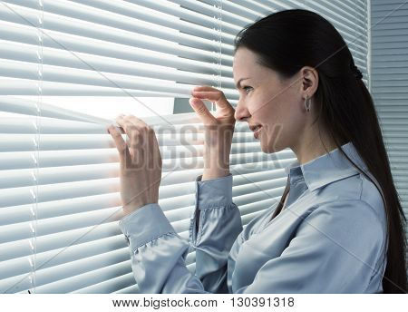 Office Worker Looking Through Window Blinds