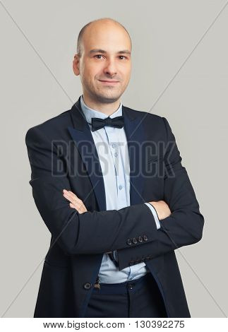 Fashionable Bald Man Wearing Black Suit And Bow Tie