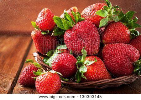 Fresh organic ripe strawberry on wooden table with water splash around
