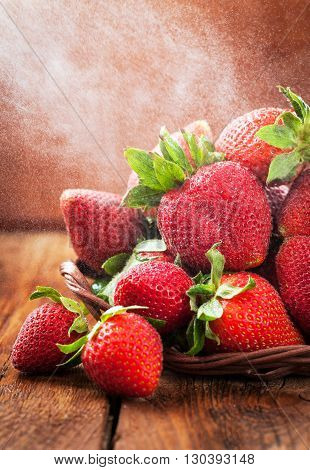 Fresh organic ripe wet strawberry on wooden table with water splash around