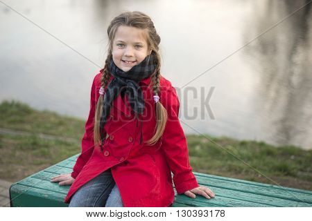 smiling girl sit on green street bench near the river